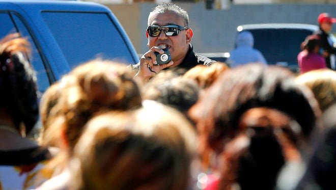 A Glendale, Ariz., police offer speaks to parents, Friday, Feb. 12, 2016, in Glendale, Ariz., after two students were shot and killed at Independence High School in the Phoenix suburb.