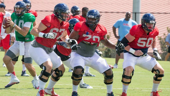 Offensive linemen Alex Givens (67), Jordan Sims (70), and Sean Rawlings (50) practice their pass protection during preseason camp.