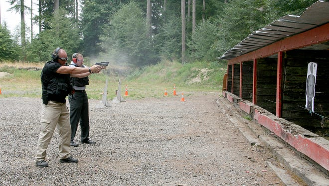 Kitsap County Sheriff's Detectives Tim Keeler (left) and Ray Stroble practice shooting at Bremerton police's range off Old Belfair Highway Thursday. The range is getting a $139,000 environmental cleanup.