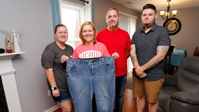 Gloria Powell is joined by daughter Emily, son Ben, and husband Dave as she shows the large pants she used to wear Thursday, May 31, 2018, in their Lafayette home. The whole Powell family has lost weight.
