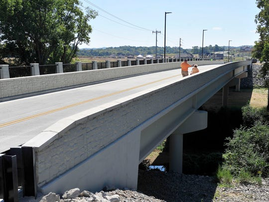 Two pedestrians walk on the new Carothers Parkway Bridge over the Harpeth River after the opening ceremony of a long-awaited Carothers extension to Long Lane in Franklin, Tenn., Wednesday, Sept. 23, 2015.