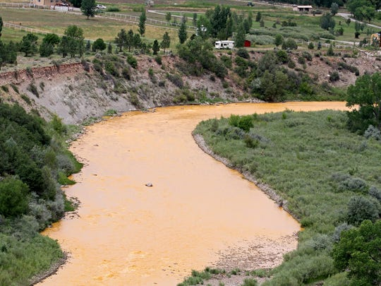 Orange sludge flows down the Animas River,  near U.S. 550 south of Durango, Colo. in August 2015.