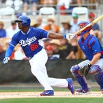Dodgers outfielder Yasiel Puig drives the ball against the Chicago Cubs in spring training.