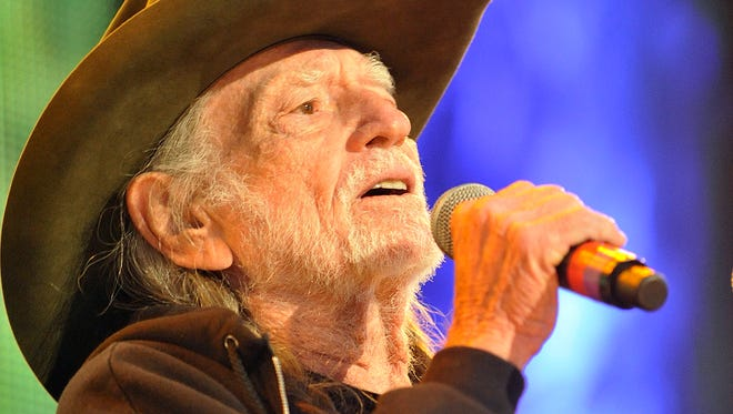 Willie Nelson introduces his band during Farm Aid in Saratoga Springs, N.Y., on Sept. 21, 2013.