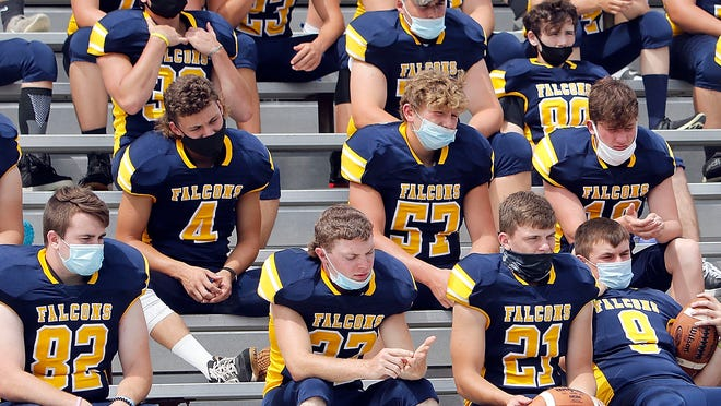 Members of the Hillsdale High School football team wear face covering as they wait for the team photo to be taken on Friday.