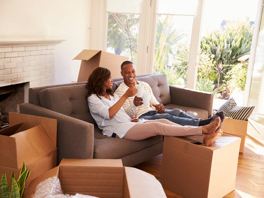 Couple On Sofa Taking A Break From Unpacking On Moving Day