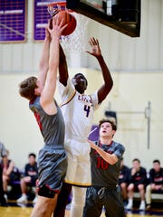 Plymouth Christian Academy senior Maximus Okolo (4) goes up for a layup during the Jan. 9 game against Dearborn Divine Child.
