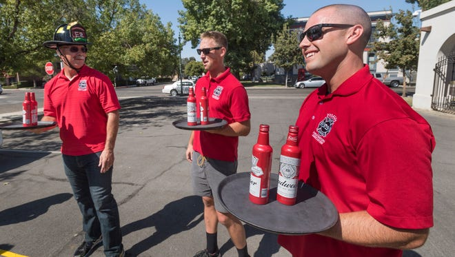 Visalia firefighters Allen Wilkinson, Chris Bailey, and Will Binder practice Wednesday for the annual Waiters Race on Thursday, August 21, 2017. Firefighters will go up against police officers to benefit charity.