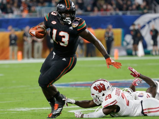 Miami running back DeeJay Dallas (13) avoids a take by Wisconsin cornerback Dontye Carriere-Williams (29) and runs for a touchdown, during the first half of the Orange Bowl NCAA college football game, Saturday, Dec. 30, 2017, in Miami Gardens, Fla. (AP Photo/Lynne Sladky)