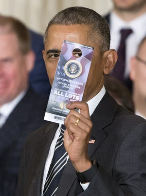 President Barack Obama holds up a United Center parking pass given to him by the Blackhawks.