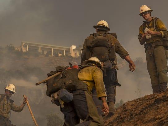 A Hot Shot crew climbs a hill while cutting a line