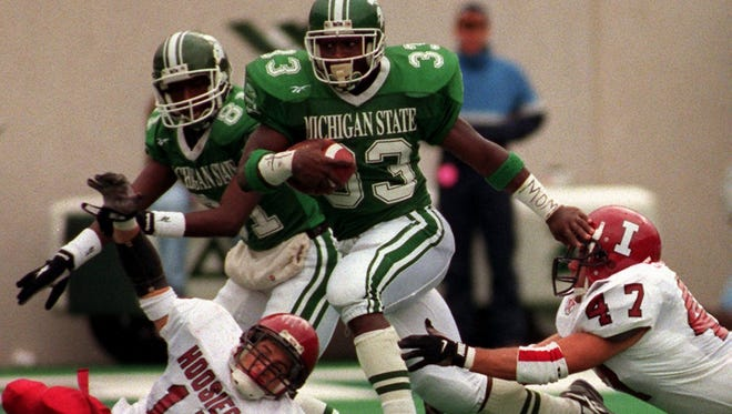 MSU's Sedrick Irvin (33) eludes Indiana defenders  as teammate Nigea Carter looks on during the Spartans' 1996 win over the Hoosiers at Spartan Stadium.