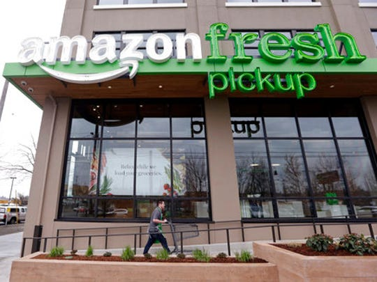 FILE - In this Tuesday, March 28, 2017, file photo, an Amazon worker wheels back a cart after loading a bag of groceries into a customer's car at an AmazonFresh Pickup location in Seattle. Amazon.com Inc. reports financial earnings Thursday, April 27, 2017.