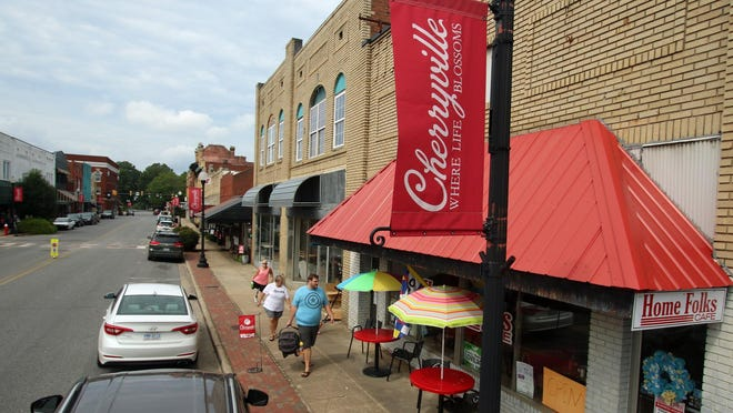People walk along the sidewalk of downtown Cherryville Friday morning, Aug. 28, 2020.