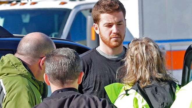 EMS personnel speak with Cody Cousins, 23, who was detained Jan. 21, 2014, after a 21-year-old teaching assistant was shot to death during class inside the Electrical Engineering Building at Purdue University in West Lafayette, Ind.