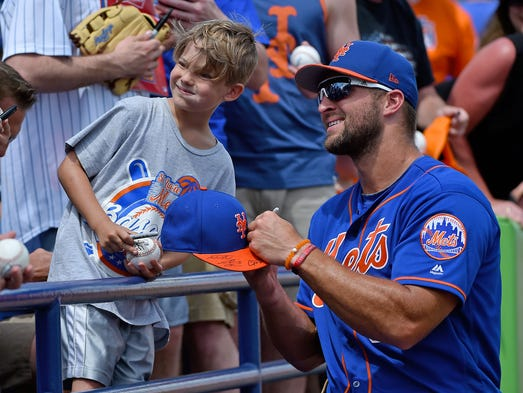 March 27: Tim Tebow signs an autograph for a young