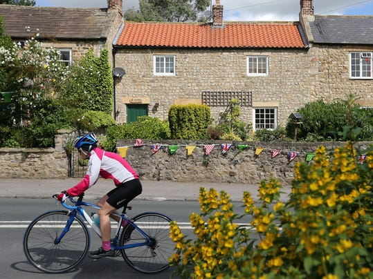 A cyclist is seen riding the official route through West Tanfield, England, Sunday, June 29, 2014, where residents of the village have created a display for the Tour De France which starts on Saturday. Tour de France fever has hit the Yorkshire Dales, with yellow bicycles appearing in hedgerows, outside pubs and in people's front gardens. The county will host the start of this year's Tour de France and as the excitement builds, bicycle-themed decorations adorn the countryside. (AP Photo/Scott Heppell)