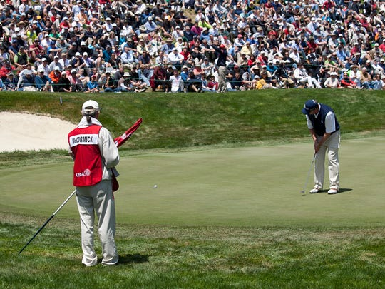 """Mark McCormick putts at the 2012 U.S. Open with Vini """"Mad Dog"""" Lopez (left) as his caddie."""