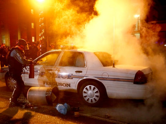 Police officers douse a police car fire after protesters