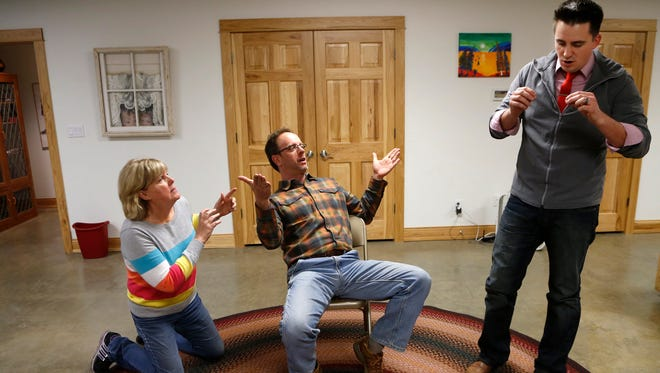 """Laurie Russell, from left, Tim Franklin and Barry Schreier of One Size Fits All perform a comedy skit called """"Sit, Stand, Kneel"""" Wednesday, February 17, 2016, during rehearsal in West Lafayette."""
