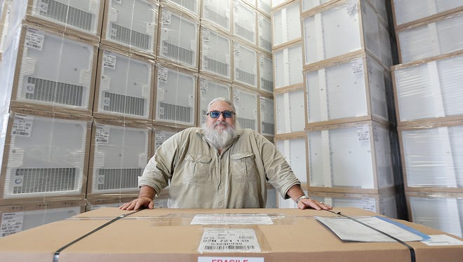 SunDanzer's El Paso General Manager Billy Amos stands near stacks of  box refrigerators that run on batteries or solar power. The El Paso facility ships the refrigerators throughout the world.