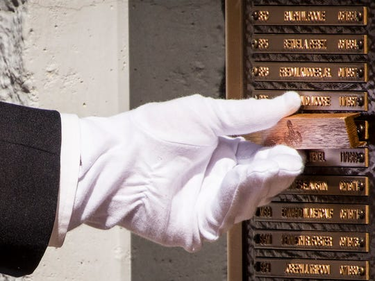A soldier removes the cover from Master Sgt. Biddle Izard Jr.'s name at the 48th annual Explosive Ordnance Disposal Memorial Service at the Kauffman EOD Training Complex at Eglin Air Force Base on May 6, 2017. Izard along with names of recent fallen and past EOD technicians are added to the memorial wall during a ceremony each year.