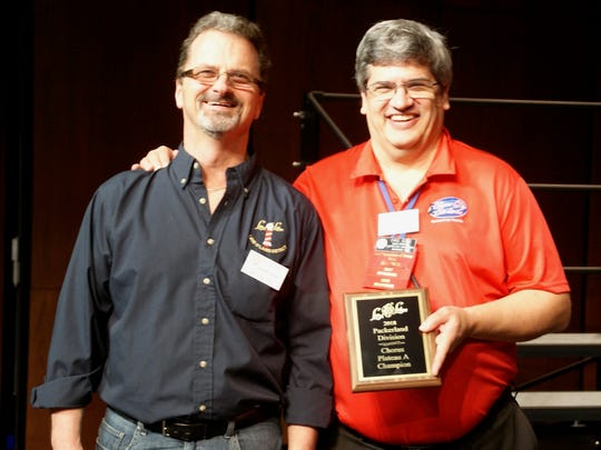 Chordsmen Director Dave Buss, receiving championship plaque from Packerland Division Vice President Scott Finley.