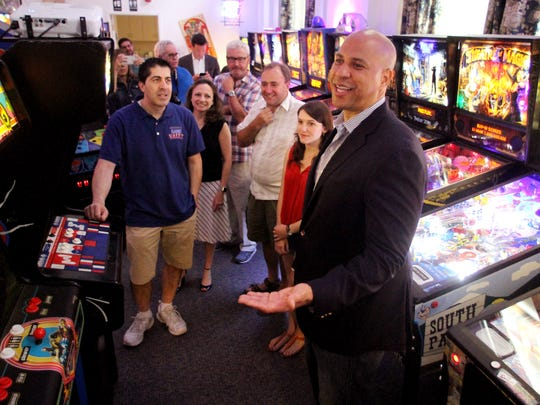 U.S. Senator Cory Booker checks out Morristown Game Vault as owner David Balsamini, l, look on as Sen. Booker took a walking tour of some of MorristownÕs finest small businesses joined by Mayor Tim Dougherty. The tour showcases a variety of businesses that all play a key role in keeping Morristown a great place to live and work.  August 5, 2017. Morristown, NJ