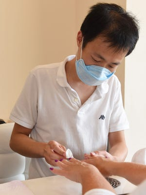 Steven Chen, 35, manager of Million Nail Spa in the Town of Poughkeepsie, finishes doing the nails of one of his customers.