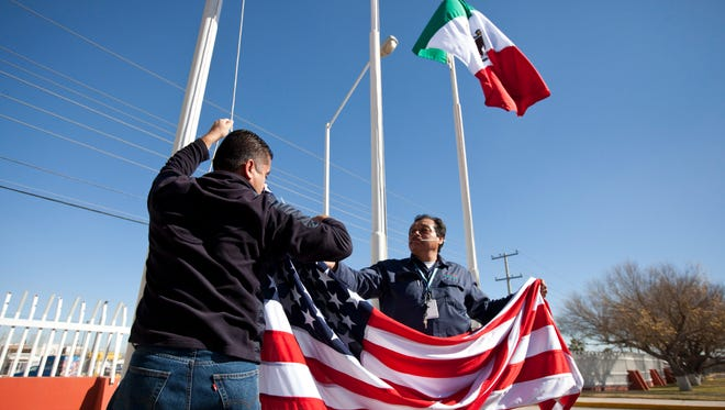 Workers at one of maquiladoras of the TECMA group prepare to raise the U.S. flag along with the Mexican and TECMA flags in Ciudad Juarez, Mexico.