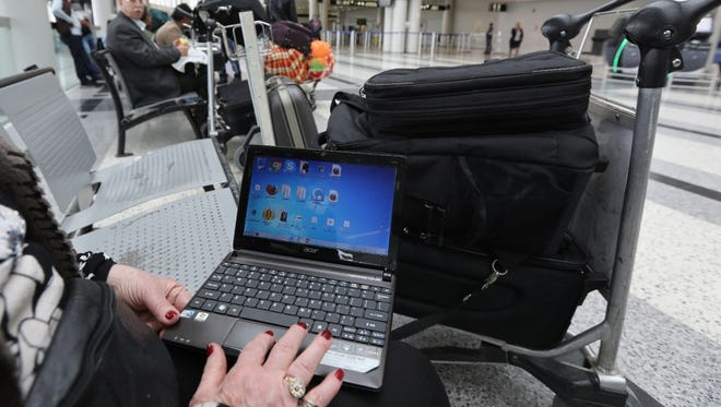 A Syrian woman traveling to the United States through Amman opens her laptop before checking in at Beirut international airport on March 22.