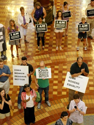 Anti-abortion and abortion-rights groups held competing signs at a rally Aug. 28, 2013, at the Iowa state Capitol in Des Moines.