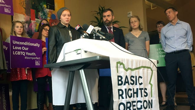 Elliot Yoder, 16, a transgender student at Dallas High School in Dallas, Ore., speaks at a news conference held by ACLU Oregon and Basic Rights in Portland, Ore., Thursday, Nov. 16, 2017, to protest a federal lawsuit filed against the Dallas School District over its policy on the treatment of transgender students. The district began allowing Yoder to use the boys' locker room and boys' restrooms after he publicly identified as transgender.