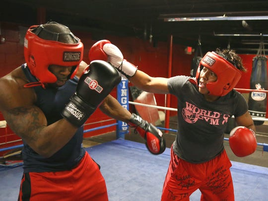 Cierra Taylor (R) spars with trainer Derick Gramling while working out at World Gym on East Ave.  Taylor, a single mother of three, will fight in the USA Olympic Boxing  Trials in Memphis, Tennessee.