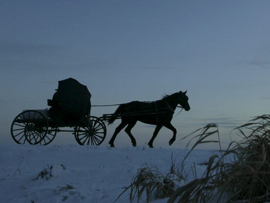 An Amish farmer shields himself from the wind as he