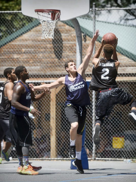 Colton Lawrence, a rising senior at Elco, tries to block a shot by Marquis Marshall during the opening day of the eighth annual Sweep the Streets Basketball Tournament at Southeast Playground in Lebanon on Saturday.