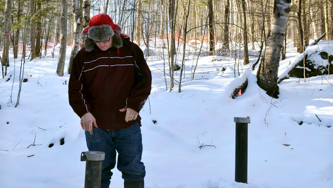 In this Friday, Dec. 16, 2016, photo, Richard Higgins, whose family's well water has been contaminated by a suspected carcinogen from a Dartmouth dump site, looks down at one of many test wells installed to monitor the groundwater in Hanover, N.H. Dartmouth College said it has spent around $8.4 million cleaning up contamination where scientists dumped carcasses of lab animals in the 1960s and 1970s.