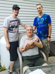 Bob Bronson sits between his grandsons, Alex and Jordan,