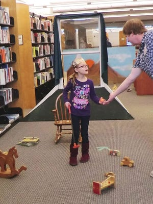 A young golfer turns over her ball after completing the Peter Pan-themed hole created by Home Schooling Performing Arts for the March Browser Open mini-golf fundraiser at the Fond du Lac Public Library.