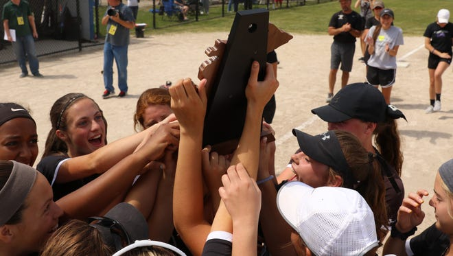Happily hoisting their district championship trophy Saturday are the Plymouth Wildcats.