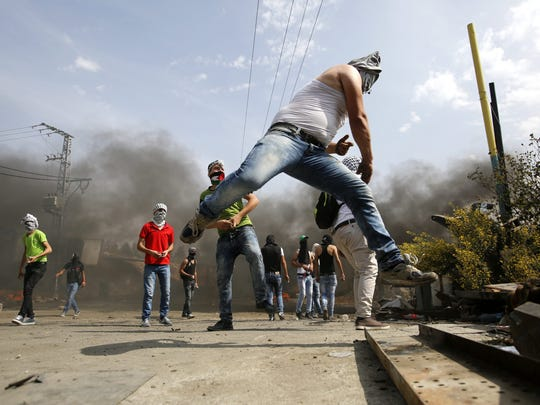 Palestinian protesters throw stones during clashes