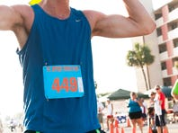 Marcus Solbakke of Oslo, Norway, flexes as he finishes in first at the Freedom 5k in Cape Coral on Saturday. Solbakke finished with a time of 17:14.