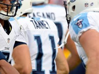 Chiefs quarterback Alex Smith, who passed for 171 yards and two touchdowns, is pressured by Titans nose tackle Al Woods during the first quarter.