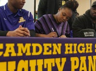 Camden High School football players Brad Hawkins (left) and Ron Johnson celebrate with Coach Dwayne Savage after signing their letters of intent to the University of Michigan on Wednesday.