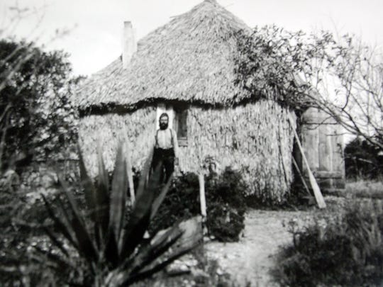 Gottlob Kroegel stands in front of the first home he