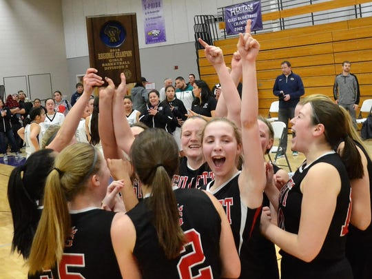 Members of the Gillett girls basketball team hold the regional title plaque aloft while celebrating their overtime victory over Oneida Nation on Monday night at Oneida National High School.