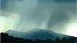 Rain from a monsoon storm is seen above mountains near