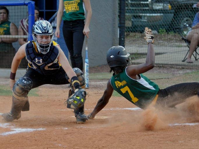Jenna Bobbitt of Navarre High playing for the Subway All-Star Girls East team can't quite make the tag on Nachelle Watson of West Florida High, a member of the All-Star West team during their game Thursday evening at the UWF softball field.   The event was the 2014 Subway All-Star Girls East vs West Softball game.