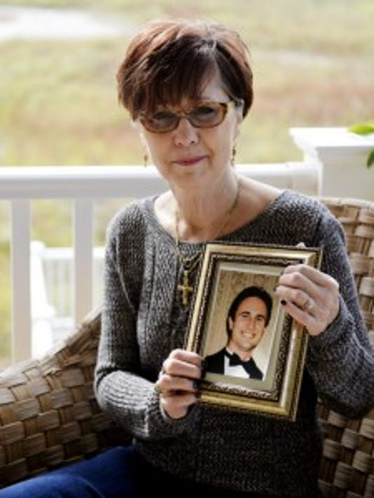 Charlene Sciarretta holds a picture of her son Danny for a portrait outside her home in October 2014. Sciarretta said the photograph is of Danny at his happiest, when he was the best man at a 2003 wedding, one year before he died. Since Danny died of a heroin overdose at age 26 in May 2005, Sciarretta has worked to promote drug abuse awareness. A member of the York County Heroin Task Force, Sciarretta has told her story many times during town hall meetings around the area.   (File photo)