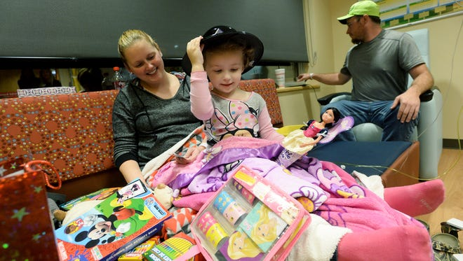 Eliie Moody, 2, adjusts her new hat as she surveys the toys given to her by troopers from the North Carolina Highway Patrol while sitting with her parents, Krystal and T.J., in her room at Mission Hospital on Tuesday, Dec. 15, 2015. Ellie is receiving ongoing treatment after having a brain tumor operated on but expects to be home for Christmas morning.